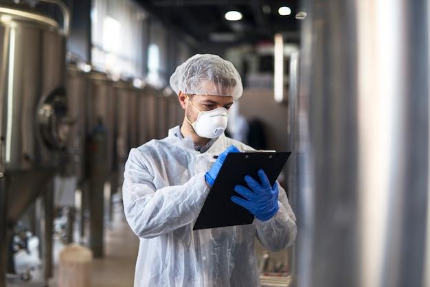 Technologe in weißer uniform, der die qualität in der industriellen produktionsfabrik überprüft