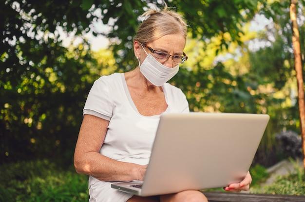 Technologie, alter leute konzept - ältere ältere frau im gesicht schutzmaske online mit laptop-computer im freien im garten arbeiten. fernarbeit, fernunterricht.