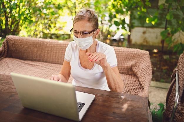 Technologie, alter leute konzept - ältere ältere frau in der schützenden gesichtsmaske verwenden drahtlose kopfhörer, die online mit laptop im freien im garten arbeiten. fernarbeit, fernunterricht.