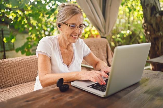 Technologie, alter leute konzept - ältere glückliche ältere frau, die drahtlose kopfhörer verwendet, die online mit laptop im freien im garten arbeiten. fernarbeit, fernunterricht.