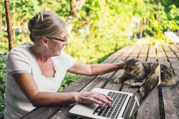Technologie, alter leute konzept - ältere glückliche ältere frau mit hauptkatze, die online mit laptop-computer im freien im garten arbeitet. fernarbeit, fernunterricht.
