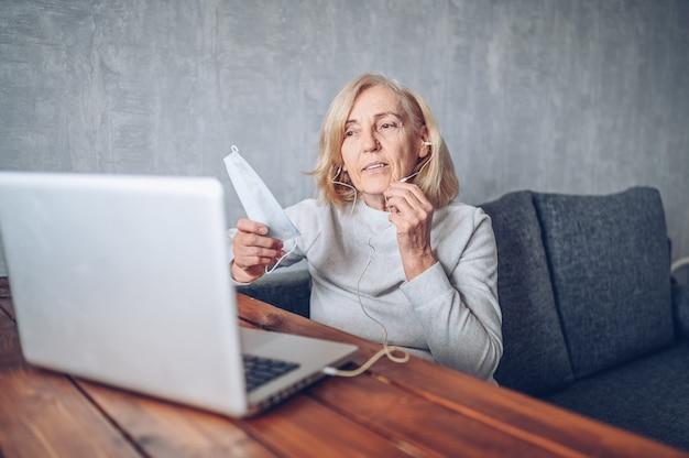 Technologie-, alters- und personenkonzept - ältere ältere frau mit gesichtsmaske, die arbeitet und einen videoanruf mit laptop-computer zu hause während der coronavirus-covid19-pandemie macht. bleib zu hause konzept