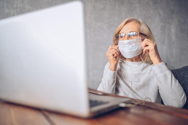 Technologie-, alters- und personenkonzept - einsame traurige ältere ältere frau im gesicht medizinische maske arbeiten und einen videoanruf mit laptop-computer zu hause während coronavirus covid19 pandemie machen. zu hause bleiben