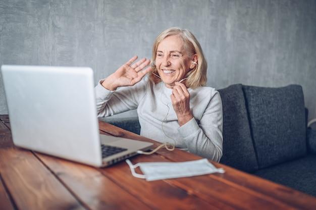 Technologie-, alters- und personenkonzept - glückliche ältere ältere frau mit gesichtsmaske, die arbeitet und einen videoanruf mit laptop-computer zu hause während der coronavirus-covid19-pandemie macht. zu hause bleiben