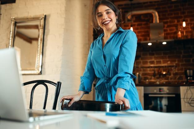 Technologie-, berufs- und fernarbeitskonzept. selbstbewusste junge texterin, die in der küche steht