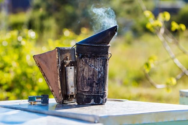 Technologie der begasung von bienen. berauschender rauch für eine sichere honigproduktion. alter bienenraucher. imkerei-tool.