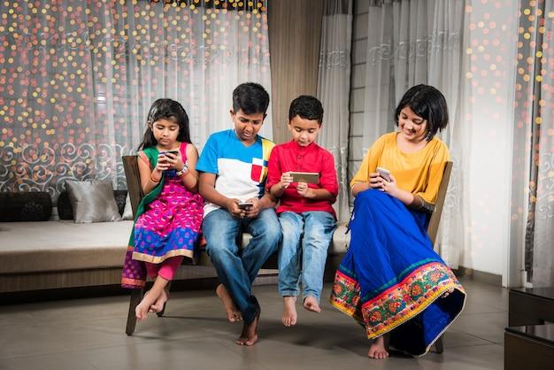 Technologie, die die indische kindheit verdirbt - kinder in traditioneller kleidung, die in der diwali-nacht mit dem smartphone beschäftigt sind, während sie drinnen auf einer couch sitzen