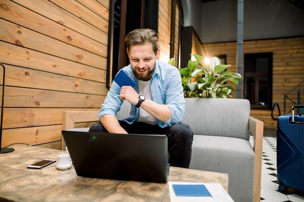 Technologie-, einkaufs-, bank-, reise- und lebensstilkonzept - schöner junger kaukasischer mann mit laptop und pass, der in der modernen hotelhalle oder im coworking sitzt