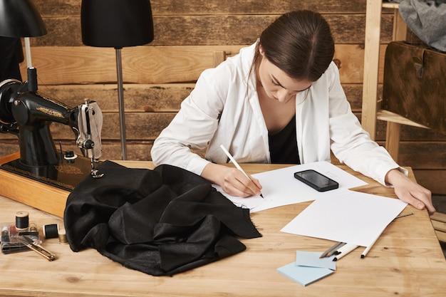 Technologie erleichtert die arbeit. porträt des fokussierten entschlossenen designers, der neues kleidungskonzept zeichnet, alles misst und mit smartphone berechnet, in der nähe von nähmaschine und stoff sitzt