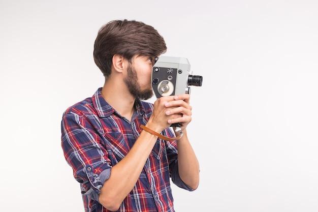Technologie-, fotografie- und people-konzept - gut aussehender mann im karierten hemd, der ein foto auf der vintage-kamera auf weißem hintergrund mit kopienraum macht