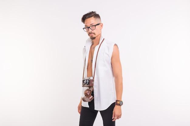 Technologie-, fotografie- und people-konzept - hübscher junger mann mit retro-kamera auf weißem hintergrund mit kopierraum