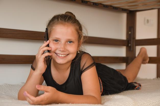 Technologie, freizeit, kommunikationskonzept. fröhlicher teenager in nachtwäsche, nutzt handy für online-chats, networking, erhält sms, liegt auf dem bett