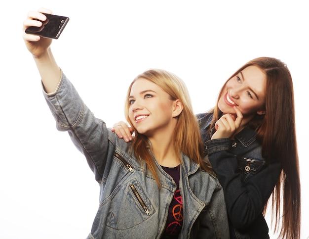 Technologie-, freundschafts- und menschenkonzept - zwei lächelnde teenager, die mit smartphone-kamera fotografieren