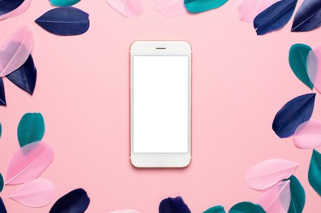 Technologie für modell mit schönen abstrakten rosa grünen und blauen federn und smartphone.