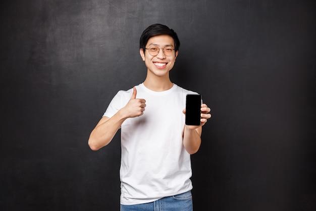 Technologie, gadgets und personenkonzept. durchsetzungsfähiger süßer asiatischer typ in t-shirt und brille, empfehlen online-shop oder anwendung für handy, zeigen daumen hoch und telefonanzeige