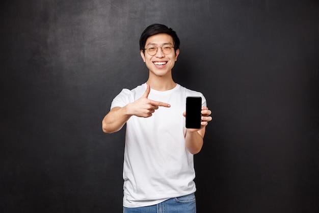 Technologie, gadgets und personenkonzept. fröhlicher asiatischer kerl in t-shirt und brille, hält handy, zeigt auf smartphone-bildschirm und lächelt zufrieden, empfehlen download-app