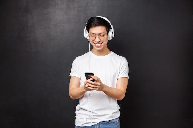 Technologie, gadgets und personenkonzept. hübscher glücklicher junger lächelnder asiatischer mann im t-shirt, musik in kopfhörern hören, wiedergabeliste im handy auswählen, freund sms schreiben,