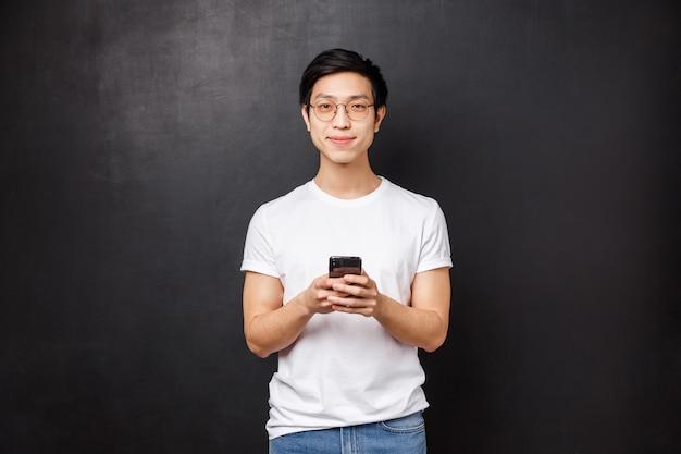 Technologie, gadgets und personenkonzept. hübscher junger entschlossener asiatischer mann im t-shirt und in der brille unter verwendung der handyanwendung, halten smartphone und lächeln in kamera,