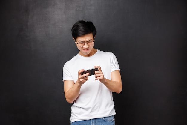 Technologie, gadgets und personenkonzept. porträt des jungen asiatischen kerls halten handy beide hände horizontal, blinzelt und runzelt die stirn, als er versucht, hartes niveau im smartphone-spiel zu bestehen