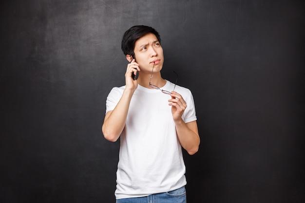 Technologie, gadgets und personenkonzept. porträt des nachdenklichen und unentschlossenen asiatischen kerls, der brillenrand beißt, während er denkt, als würde er auf dem handy sprechen und die schwierige wahl treffen, welche bestellung über smartphone