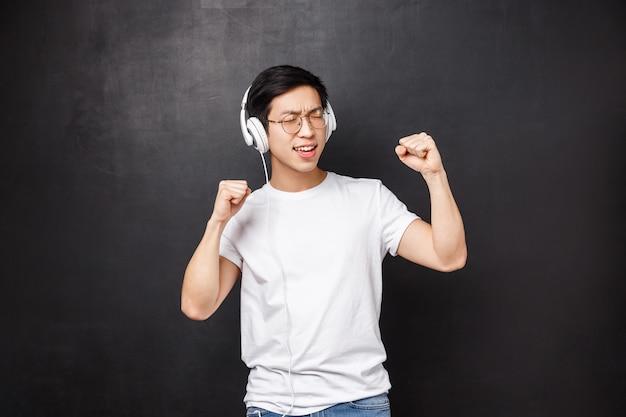 Technologie, gadgets und personenkonzept. sorgloser hübscher junger asiatischer mann, der fantastisches neues lied des lieblingskünstlers hört und musik in kopfhörern genießt, die mit geschlossenen augen tanzen