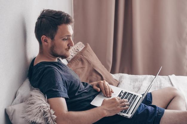 Technologie-, haus- und lebensstilkonzept - nahaufnahme des mannes, der mit laptop arbeitet und zu hause auf sofa sitzt. junger mann, der seinen laptop mit lächeln benutzt, während er zu hause auf dem bett sitzt