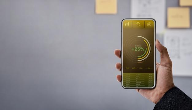 Technologie im finanz- und geschäftsmarketing-konzept. grafiken und diagramme werden auf dem bildschirm des smartphones angezeigt.