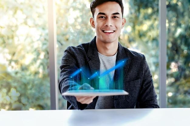 Technologie im geschäftskonzept. glücklicher mann, der hohes gewinn-diagramm in digital-tablet darstellt