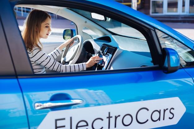 Technologie in maschinen. schöne attraktive ernsthafte frau, die hinter dem lenkrad sitzt und einen knopf auf der sensorplatte drückt, während sie ihr auto startet
