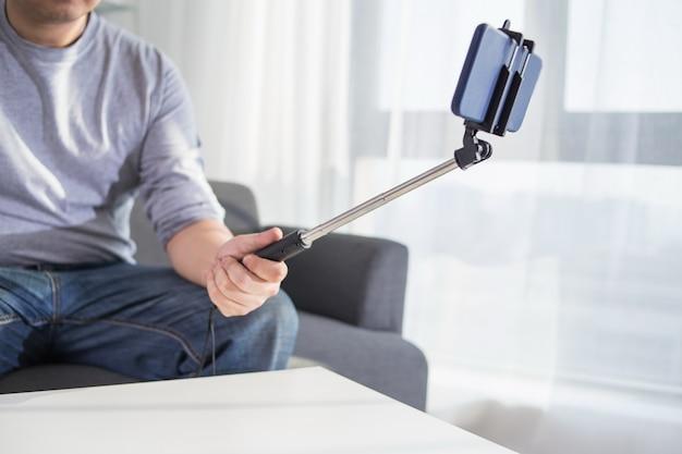 Technologie internet und glück konzept. junge frau lustige mädchen, die selbstbild selfie mit smartphone-kamera auf stick beim sitzen auf sofa zu hause