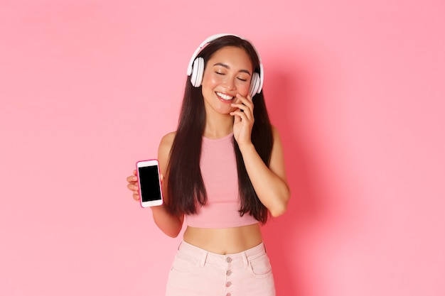 Technologie-, kommunikations- und online-lifestyle-konzept. schönes, verträumtes asiatisches mädchen in kopfhörern, geschlossenen augen und alberner berührender wange, tagträumen beim musikhören, mobiler bildschirm zeigend