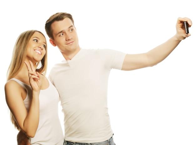 Technologie-, liebes- und freundschaftskonzept - lächelndes paar mit smartphone, selfie und spaß. studioaufnahme auf weißem hintergrund.