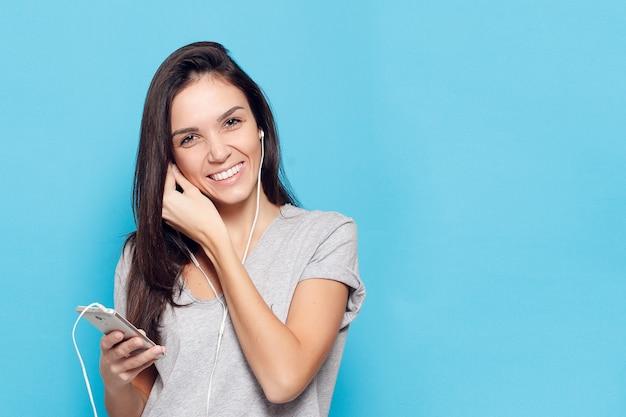Technologie, lifestyle, internetsucht und menschenkonzept - junge schöne frau mit smartphone. fröhliche frau mit kopfhörern auf blauem hintergrund. glückliche und lächelnde attraktive frau