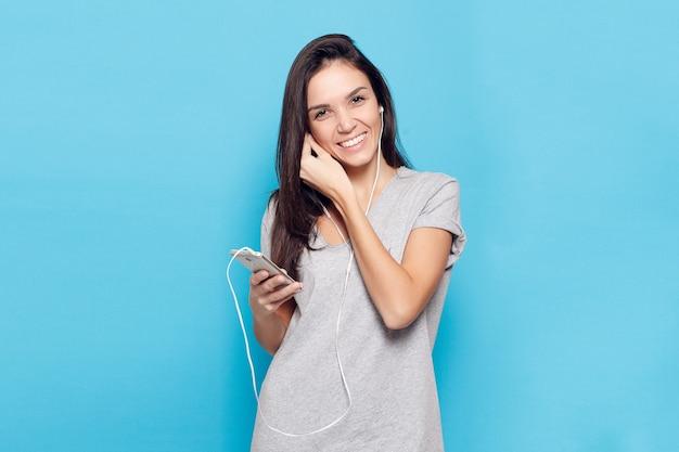 Technologie, lifestyle, internetsucht und menschenkonzept - junge schöne frau mit smartphone. fröhliche frau mit kopfhörern auf blauem hintergrund