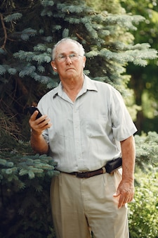 Technologie-, menschen- und kommunikationskonzept. älterer mann im sommerpark. grangfather benutzt ein telefon.