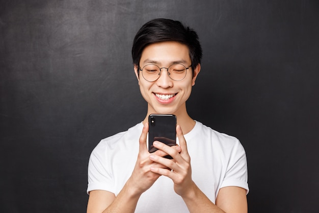 Technologie-, messaging- und personenkonzept. nahaufnahmeporträt des fröhlichen jungen asiatischen mannes, der am handy lächelt, video im internet sieht, gute nachrichten per e-mail erhält,