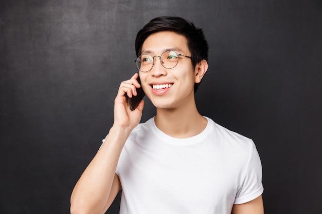 Technologie-, messaging- und personenkonzept. nahaufnahmeporträt des sorglosen asiatischen kerls in der brille, am telefon sprechend, lächelnd und weg schauend, während konversation, anruf für termin
