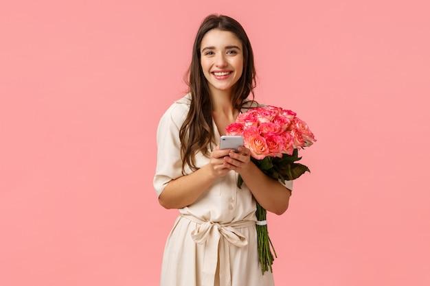 Technologie-, romantik- und glückskonzept. zarte junge fröhliche lächelnde frau mit schönen blumen, telefon haltend, antwort auf glückwunsch b-tag, chat am geburtstag, rosa wand