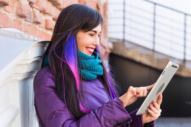 Technologie-, stadt- und personenkonzept - studentische junge frau, die ein ebook oder tablet in einer stadt liest