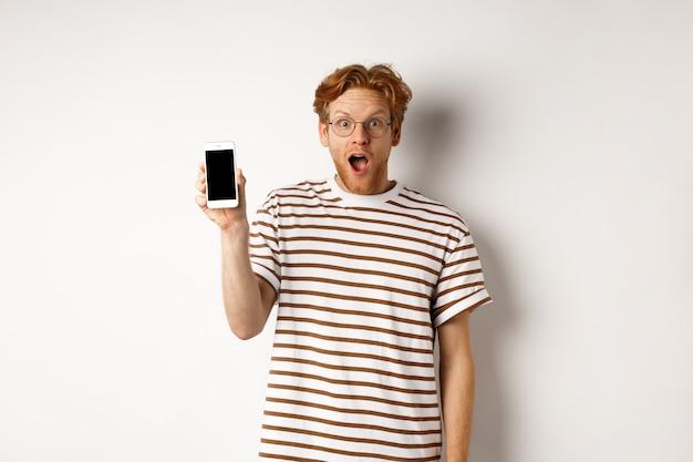 Technologie- und e-commerce-konzept. überraschter und schockierter rothaariger kerl, der online-werbung auscheckt und leeren smartphonebildschirm und kiefer zeigt, weißer hintergrund