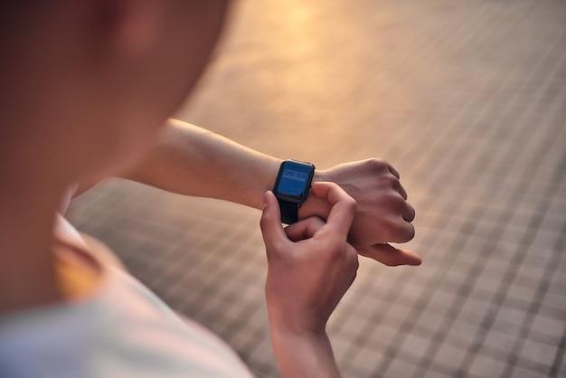 Technologie und fitness nahaufnahme eines jungen mannes, der während des trainings die zeit auf der smartwatch überprüft