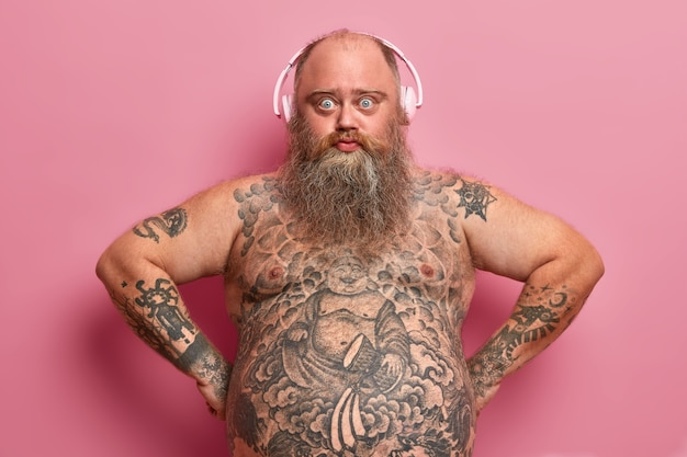 Technologie- und lifestyle-konzept. ernsthafter selbstbewusster praller mann trägt kopfhörer, hört musik, hat tätowierten körper, fetten bauch, dicken bart, posiert gegen rosa wand, fand große wiedergabeliste