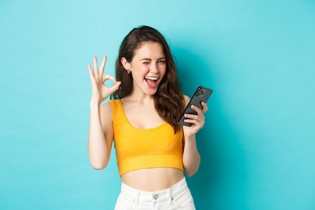 Technologie- und lifestyle-konzept. fröhliches brünettes weibliches modell sagt ja, zwinkert und zeigt ein okayzeichen, hält das handy und steht über blauem hintergrund.