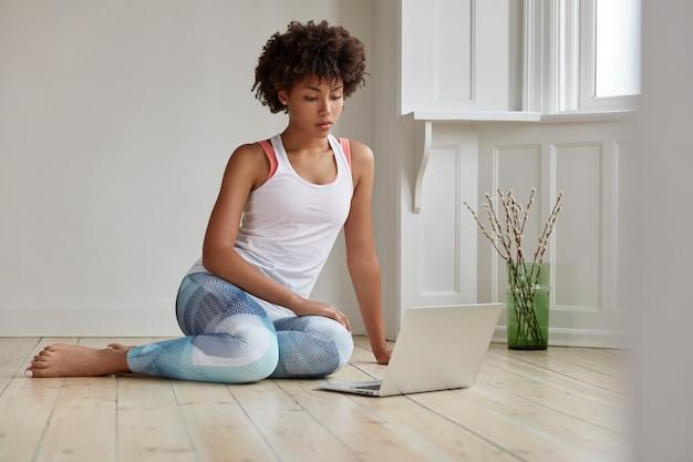 Technologie- und lifestyle-konzept. konzentrierte schwarze junge frau, die ein video auf einem laptop-computer sieht