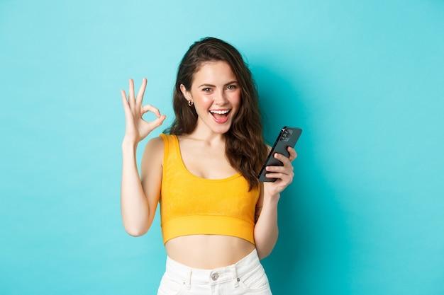Technologie- und lifestyle-konzept. selbstbewusste attraktive frau sagt ja, zeigt ein gutes zeichen für etwas online, hält smartphone und steht auf blauem hintergrund.