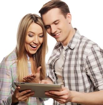 Technologie- und menschenkonzept - glückliches junges paar, das tablet-pc-computer hält