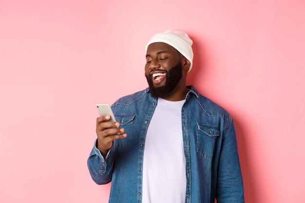 Technologie und online-shopping-konzept. glücklicher schwarzer bärtiger mann, der nachricht liest und lächelt, mit smartphone vor rosa hintergrund