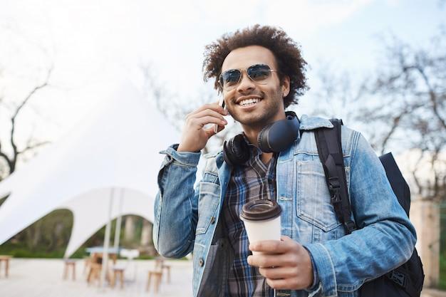 Technologie- und personenkonzept. junger hübscher dunkelhäutiger mann mit borsten- und afro-haarschnitt, der auf handy spricht, während kaffee trinkt und durch stadt geht, rucksack und jeansmantel tragend.