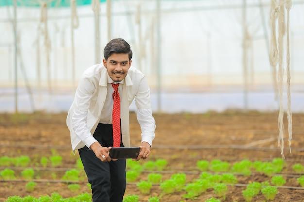 Technologie- und personenkonzept, junger indischer agronom, der tablette am gewächshaus verwendet