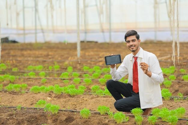 Technologie- und personenkonzept, junger indischer agronom, der tablette oder smartphone am gewächshaus zeigt